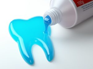 blue toothpaste coming out of tube in the shape of a tooth