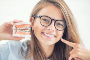 Teen holding a dental demonstration model with braces while pointing to her white teeth and smiling