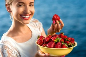 Woman holding strawberries after teeth whitening.