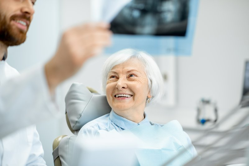 Implant dentist showing smiling patient their X-ray