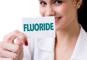 Dentist holding a fluoride card